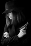 Beautiful elegant woman in black suit and black hat holding gun Stock Photos