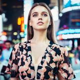 Beautiful elegant woman with blue eyes walking in night city wearing evening makeup and stylish dress. stock photos