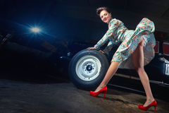 Beautiful elegant woman. Change the wheel of car in pin up style Stock Images