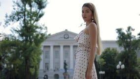 Beautiful elegant woman in dress walking at summer city. Beautiful attractive elegant woman in dress walking at summer city stock footage