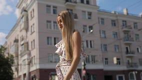 Beautiful elegant woman in dress walking at urban summer city. Beautiful attractive elegant woman in dress walking along urban summer city stock video footage