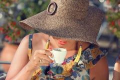Beautiful Elegant Woman Drinking Coffee. Woman in elegant  hat drinking coffee. Focus on lips Royalty Free Stock Photo