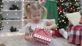 Beautiful elegant woman gives New Year`s gift to a little girl stock footage