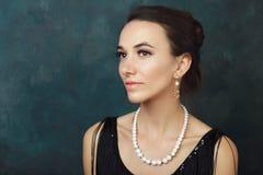 Beautiful elegant woman. Half length portrait of beautiful young elegant woman with pearls in black dress posing next to color background Royalty Free Stock Photos