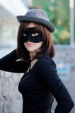 Beautiful elegant woman in a hat and carnival mask Royalty Free Stock Images