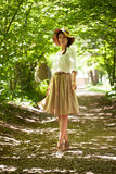 Beautiful elegant woman in a hat among green foliage Royalty Free Stock Photography