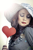 Beautiful elegant woman in hat holding heart in her hands and sm. Love and celebrate concept.Beautiful elegant woman in hat holding heart in her hands and Stock Images