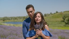 Couple inhaling fresh aroma of lavender flowers. Beautiful elegant woman inhaling fresh aroma of lavender flowers while loving african american man embracing stock footage