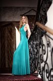 Beautiful elegant woman in a long green dress. Is stands on a staircase near the forged handrails stock photography