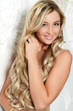 Beautiful elegant woman with long hair at a white wall Stock Image