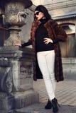 Beautiful elegant woman in luxurious fur coat posing in castle Stock Photography