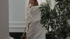 Beautiful elegant woman throwing dress near building columns. Beautiful elegant woman model throwing dress posing near building columns stock footage