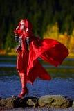 Beautiful elegant woman by mountain lake in autumn Royalty Free Stock Image