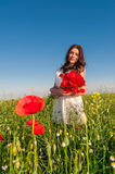 Beautiful elegant woman over Sky and Sunset in the field holding a poppies bouquet, smiling. Royalty Free Stock Image