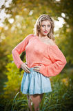 Beautiful elegant woman in pink sweater in autumn park . Stock Images