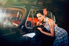 Beautiful elegant woman. Put lipstick on her lips near car mirror Royalty Free Stock Image