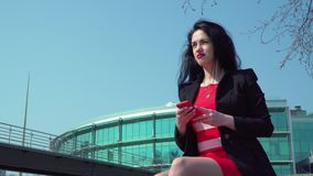 Beautiful elegant woman in red dress using phone at business center background. Beautiful elegant woman wearing red dress using her phone at office center stock footage