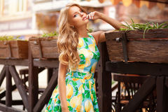 Beautiful elegant woman in romantic dress over cafe with flowers. Street fashion style Royalty Free Stock Images