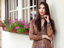 Beautiful elegant woman in romantic dress over the wall with flo. Wers. Street fashion style Royalty Free Stock Photos