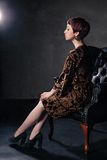 Beautiful elegant woman sitting on an armchair Royalty Free Stock Images
