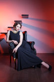 Beautiful elegant woman sitting on an armchair Royalty Free Stock Photo