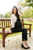 Beautiful elegant woman sitting on the bench looking away. Stock Image