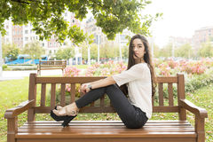 Beautiful and elegant woman sitting on bench, outdoor. Stock Photos