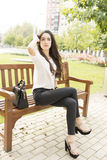 Beautiful and elegant woman sitting on bench in the park. Stock Images