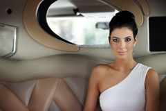 Beautiful elegant woman sitting in limousine royalty free stock photo