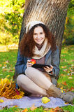 Beautiful elegant woman sitting  with tablet and apple in a park in autumn Stock Photography