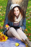 Beautiful elegant woman sitting  with tablet and apple in a park in autumn Stock Images