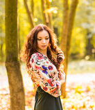 Beautiful elegant woman standing in an autumn park Royalty Free Stock Images