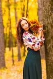 Beautiful elegant woman standing in an autumn park Stock Photo