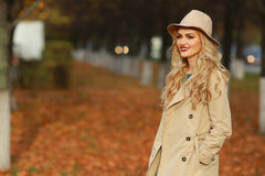 Beautiful elegant woman standing in fashionable beige hat in a park in autumn. free space Stock Image