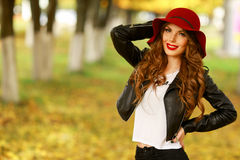 Beautiful elegant woman standing in fashionable red Hat in a park in autumn. Stock Photo