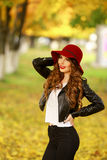 Beautiful elegant woman standing in fashionable red Hat in a park in autumn. Royalty Free Stock Photos