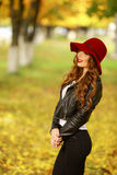 Beautiful elegant woman standing in fashionable red Hat in a park in autumn. Stock Images