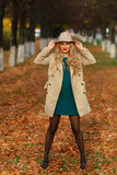 Beautiful elegant woman standing full length in fashionable beige hat in a park in autumn Stock Photography