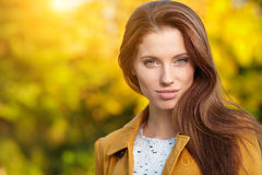 Beautiful elegant woman standing in a park in autumn Royalty Free Stock Image
