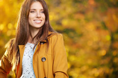 Beautiful elegant woman standing in a park in autumn Royalty Free Stock Images