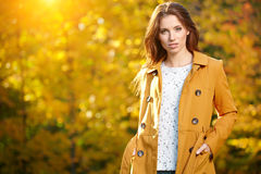 Beautiful elegant woman standing in a park in autumn Stock Photos