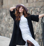Beautiful elegant woman in stylish trendy black coat and hat ove. R brick wall. Glamour lady with european look Stock Image