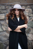 Beautiful elegant woman in stylish trendy black coat and hat ove. R brick wall. Glamour lady with european look Royalty Free Stock Photos