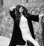 Beautiful elegant woman in stylish trendy black coat and hat ove Stock Image