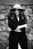 Beautiful elegant woman in stylish trendy black coat and hat ove Stock Photography