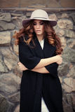Beautiful elegant woman in stylish trendy black coat and hat ove Stock Photos