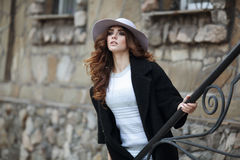 Beautiful elegant woman in stylish trendy black coat and hat ove Royalty Free Stock Images