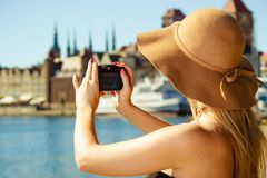 Beautiful elegant woman taking pictures with camera. Tourism, artistic, elegant fashion. Woman in elegant outfit and sun hat taking pictures Royalty Free Stock Photos