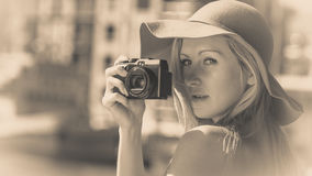 Beautiful elegant woman taking pictures with camera Stock Images