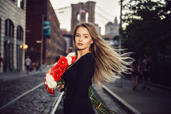 Beautiful elegant woman walking with rose flower bouquet on city street Royalty Free Stock Photography